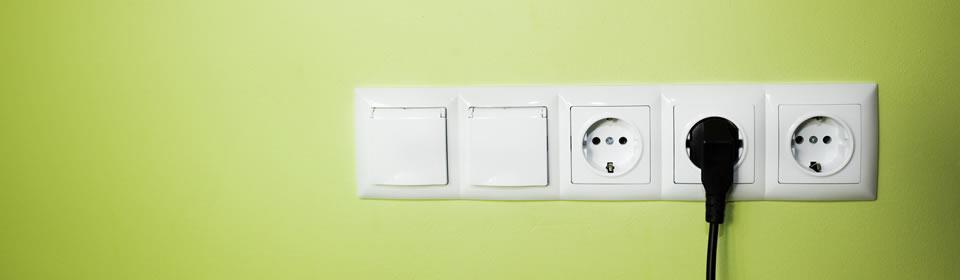 stopcontacten en lichtknoppen bij groene muur
